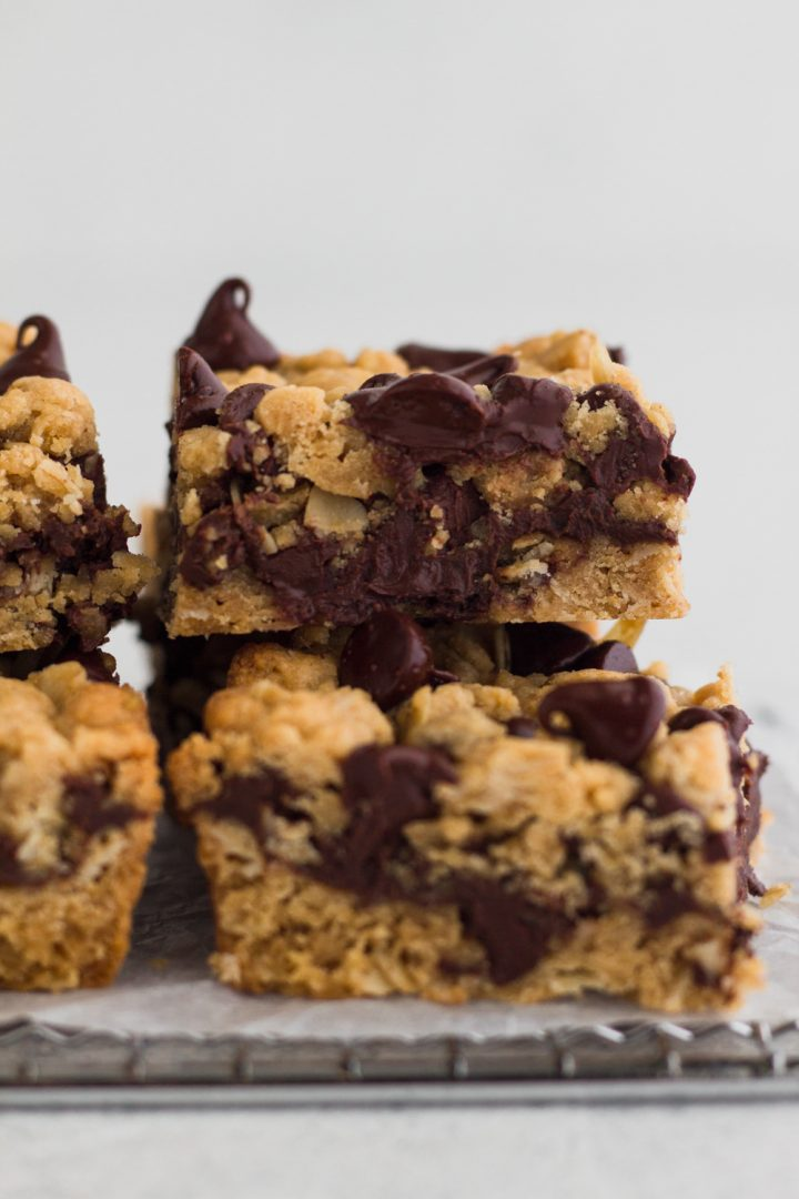 side view of chocolate peanut butter oatmeal bars stacked on a cooling rack