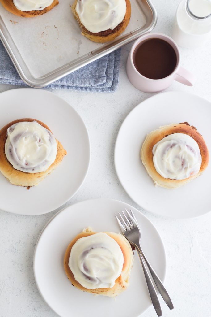 overhead view of small batch overnight cinnamon rolls on white plates with a blue cloth napkin, a pink coffee mug, and a white background