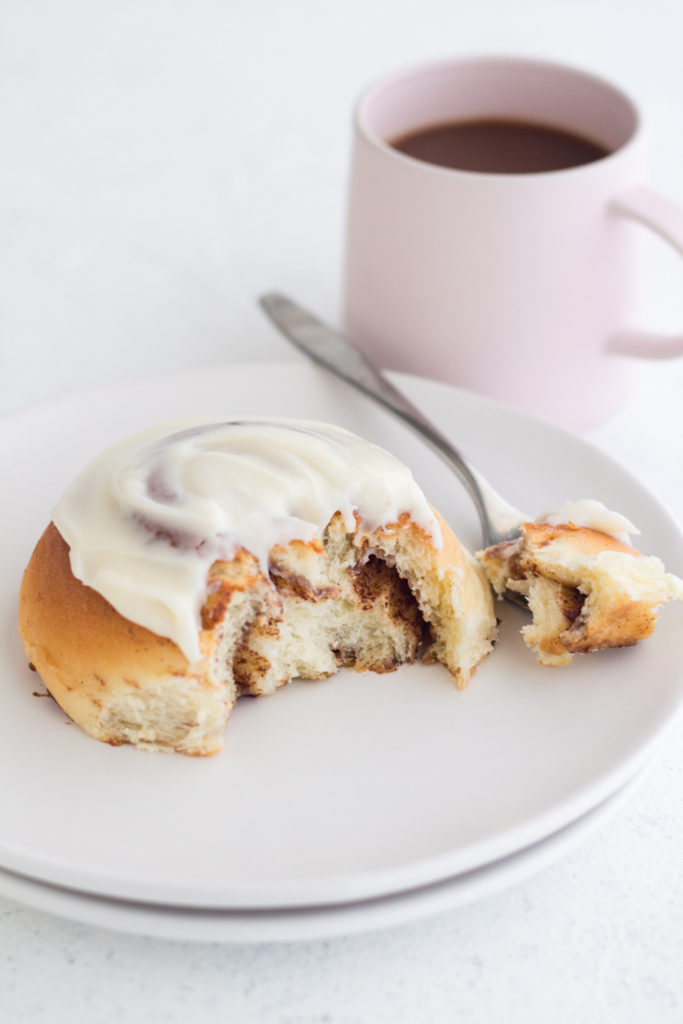 side view of cinnamon roll on a white plate with a pink coffee mug