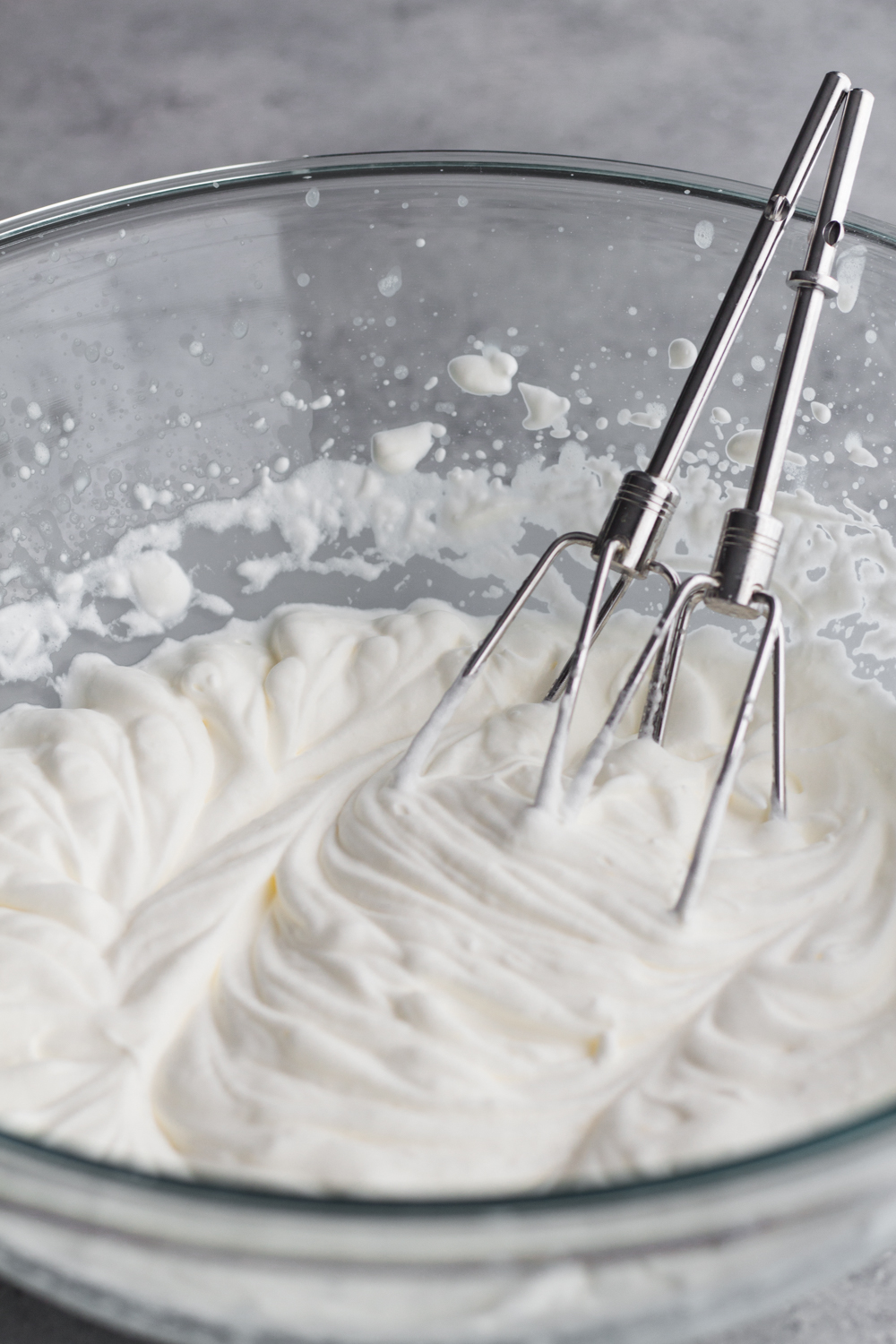 homemade whipped cream with beaters in a glass bowl on a gray surface