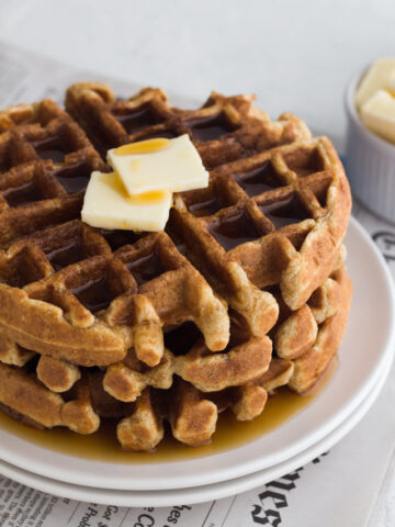 angled view of whole wheat buttermilk waffles on a white plate
