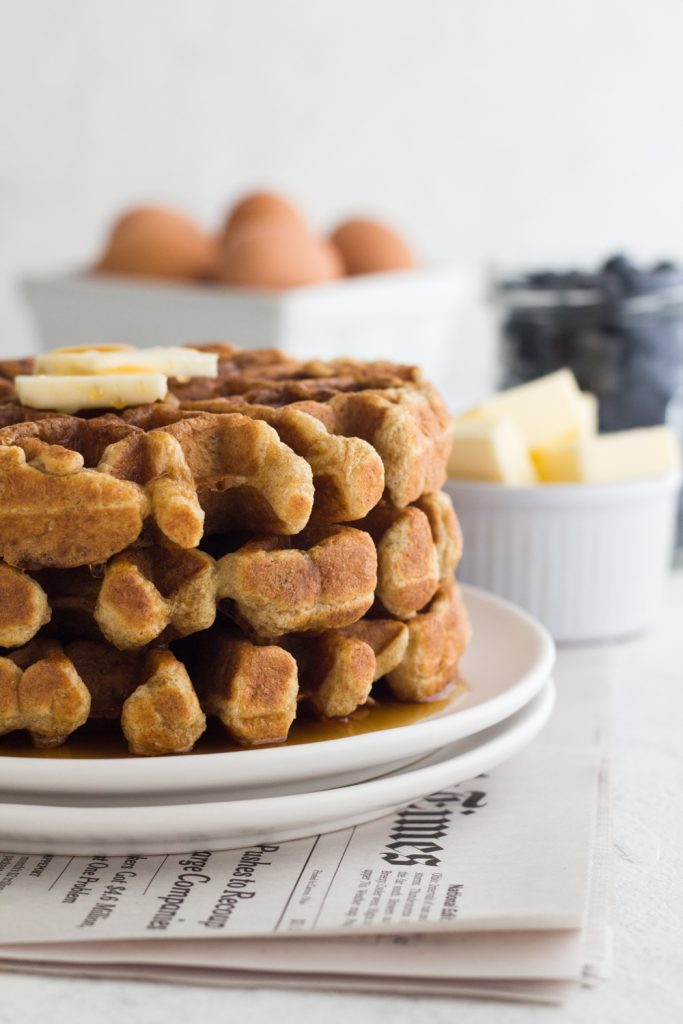 side view of whole wheat buttermilk waffles on a white plate with pats of butter, blueberries, and a crate of eggs