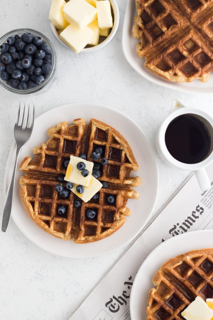 Overhead view of whole wheat buttermilk waffles with blueberries on a white plate and a white surface