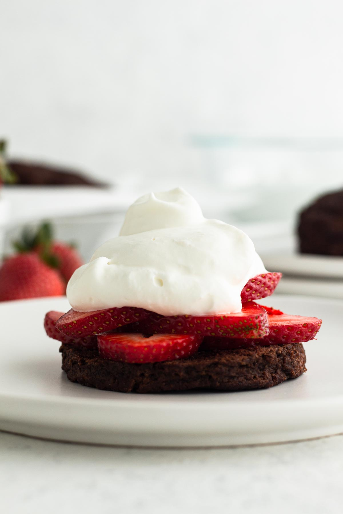 close up side view of a chocolate buttermilk biscuit topped with fresh strawberries and homemade whipped cream on a white plate