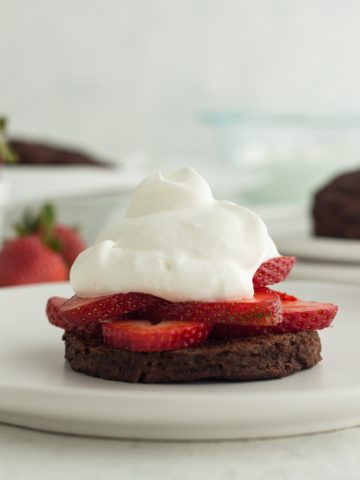 close up side view of chocolate strawberry shortcake (a chocolate buttermilk biscuit topped with fresh strawberries and homemade whipped cream) on a white plate with a white background