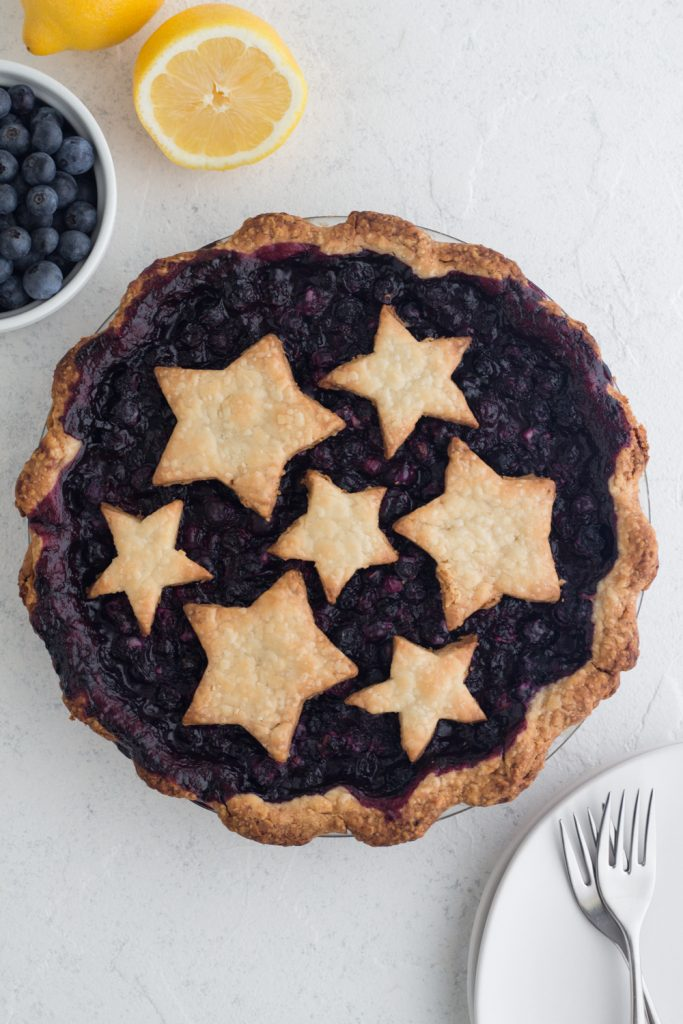overhead view of a homemade classic blueberry pie with star pie crust toppers on a white surface surrounded by fresh blueberries, lemons, and white plates