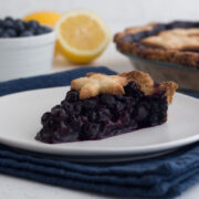 side view of a slice of homemade classic blueberry pie on a white plate atop a navy blue napkin