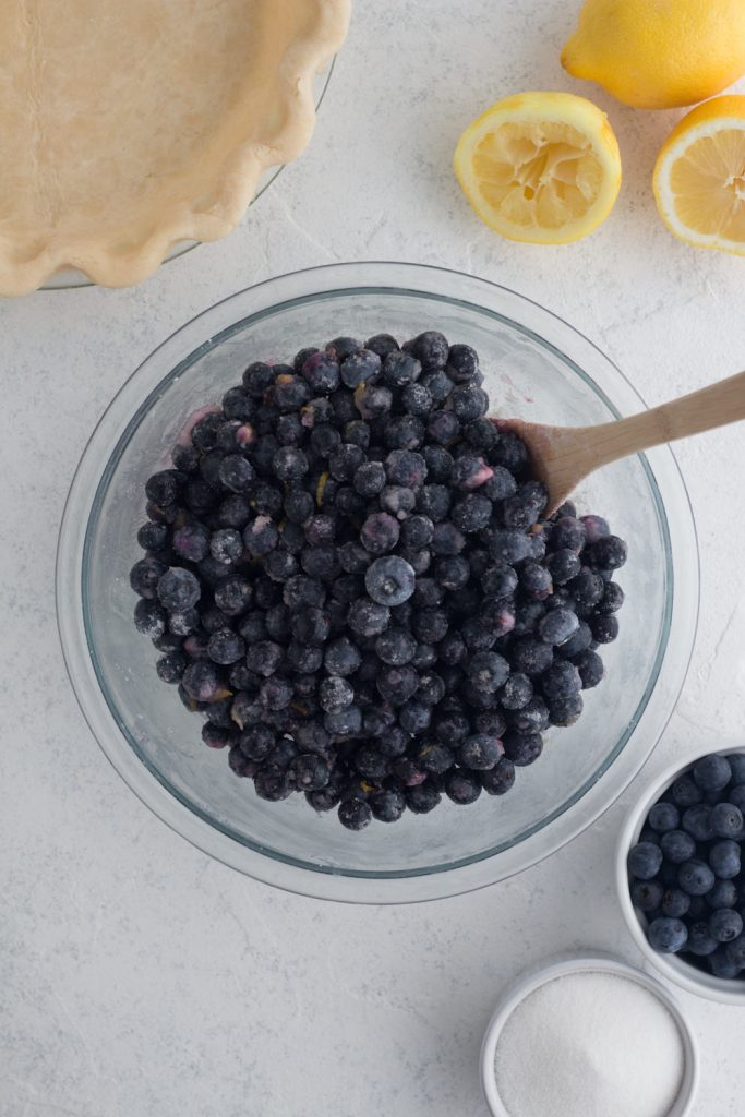 overhead view of homemade blueberry pie filling in a glass bowl on a white surface surrounded by fresh blueberries, sugar, lemons, and pie crust