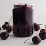 side view of homemade cherry sauce in a glass jar surrounded by fresh cherries on a white surface