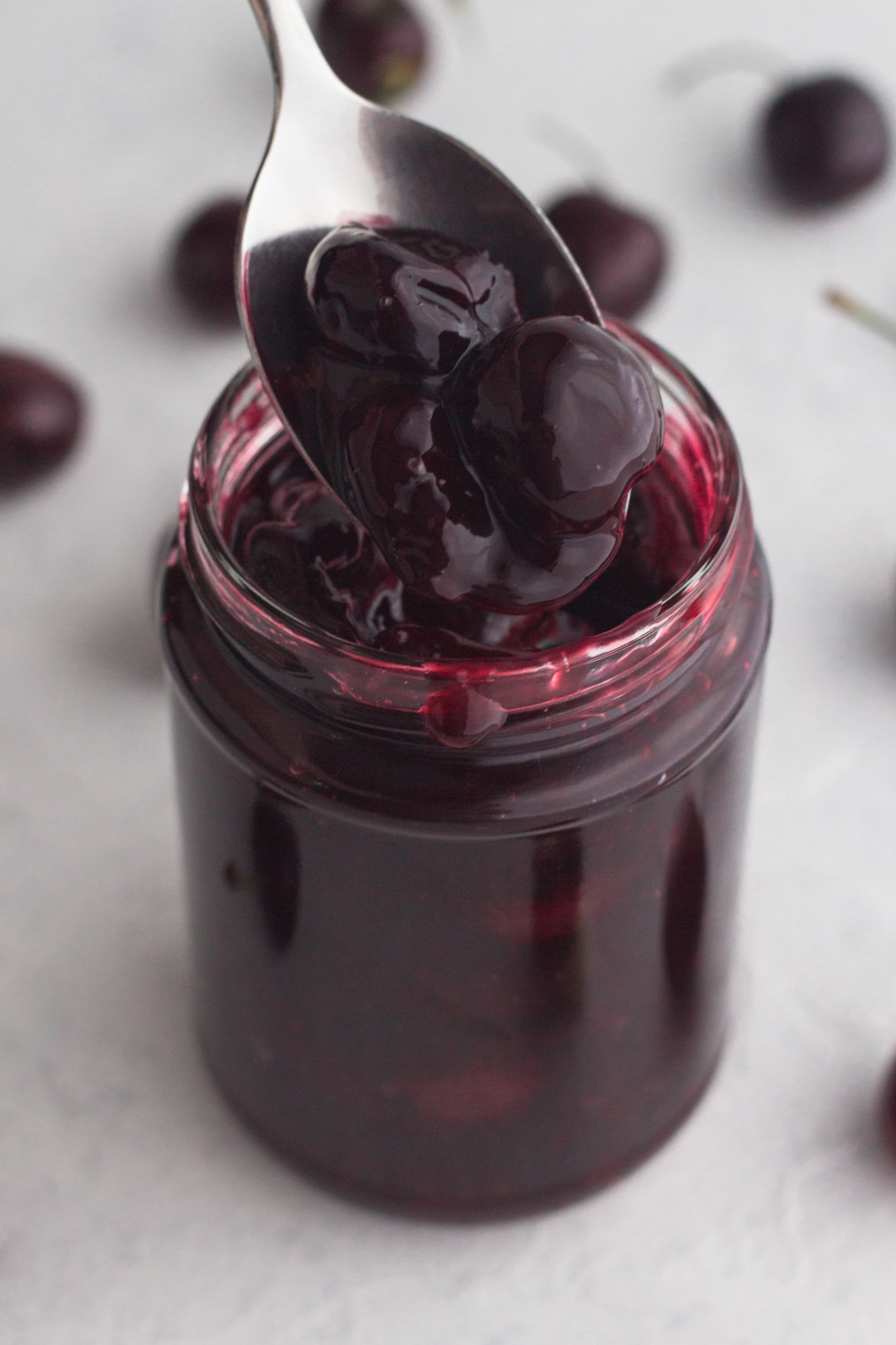 angled view of homemade cherry sauce in a glass jar with a spoon scooping the sauce