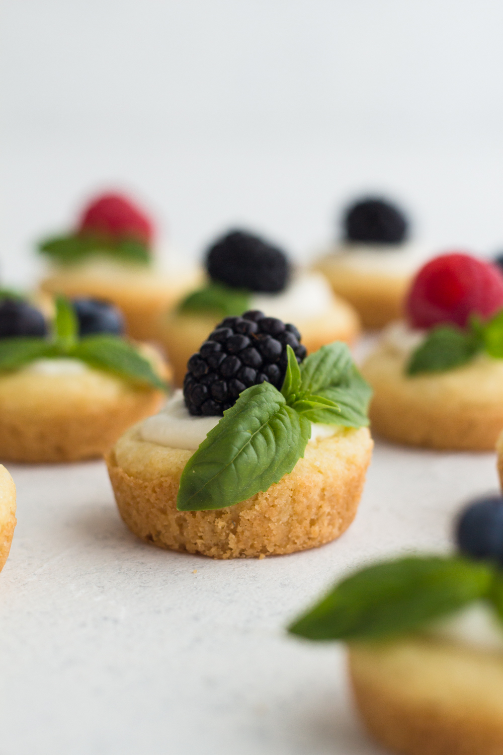 side view of sugar cookie cups filled with no bake cheesecake and topped with blackberry on a white surface