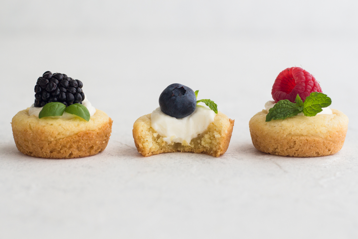 side view of sugar cookie cups filled with no bake cheesecake and topped with fresh berries and herbs