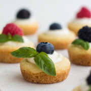 side view of mini summer fruit tarts on a white surface