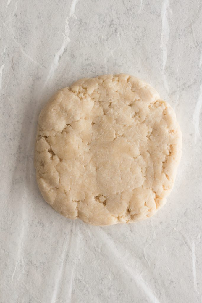 overhead view of pie crust dough formed into a disk on plastic wrap