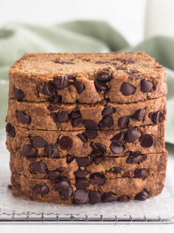 side view of slices of chocolate chip zucchini bread stacked on a cooling rack with a green linen napkin