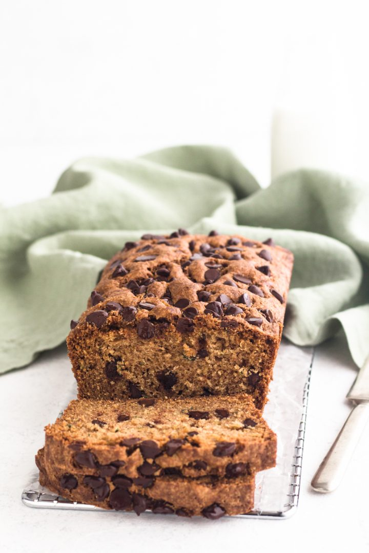 angled view of sliced chocolate chip zucchini bread on a cooling rack atop a white surface with a green linen napkin