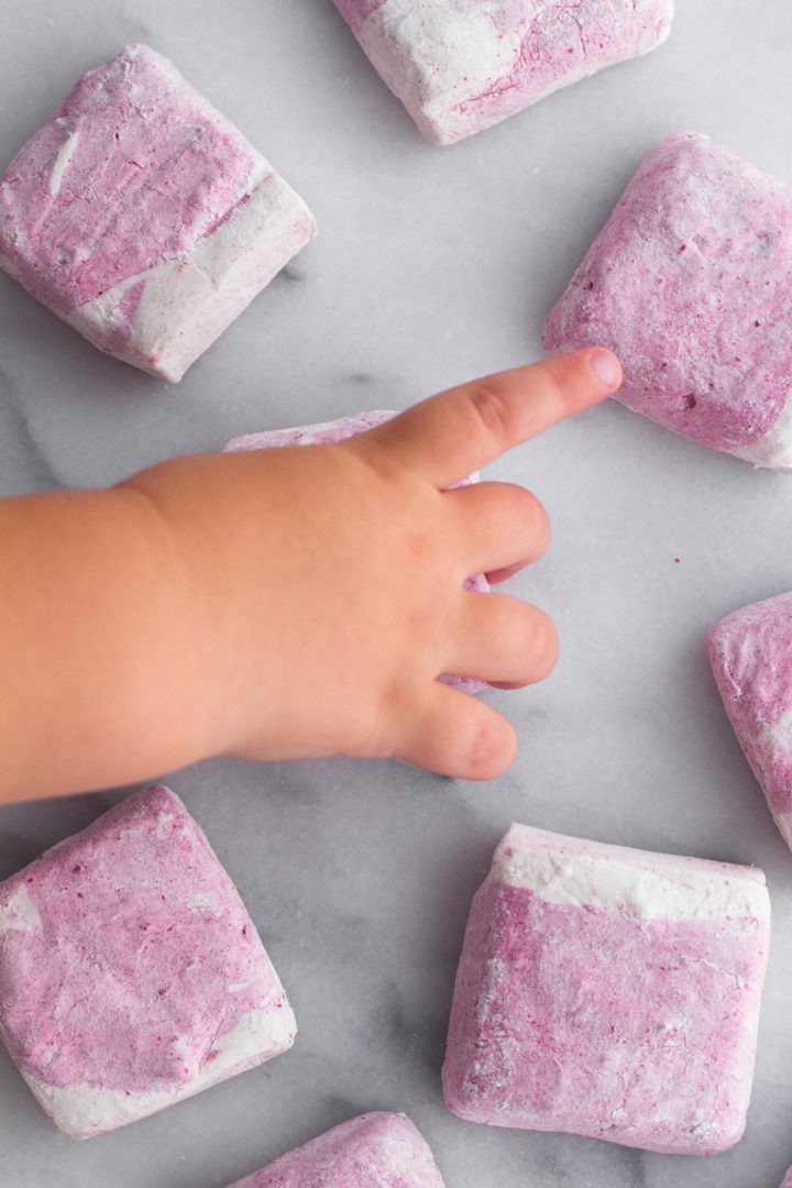 overhead view of a toddler hand reaching for a homemade raspberry swirl marshmallow on a marble surface