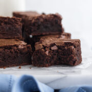 side view of a bitten brownie stacked on a white marble surface with a blue linen and a glass of milk