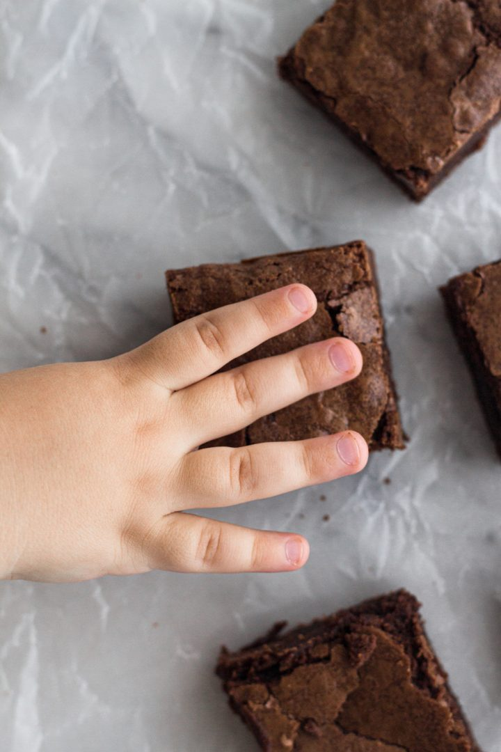 overhead view of a toddler's hand reaching for a brownie on a white marble surface