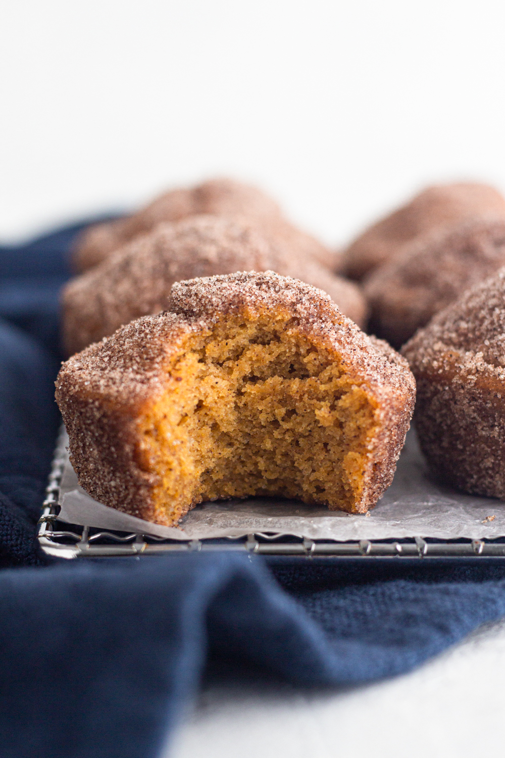 side view of a bitten pumpkin spice donut muffin on a cooling rack with a navy blue linen napkin
