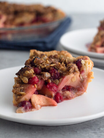 slice of apple cranberry crumb pie on a white plate with the pie and another slice in the background