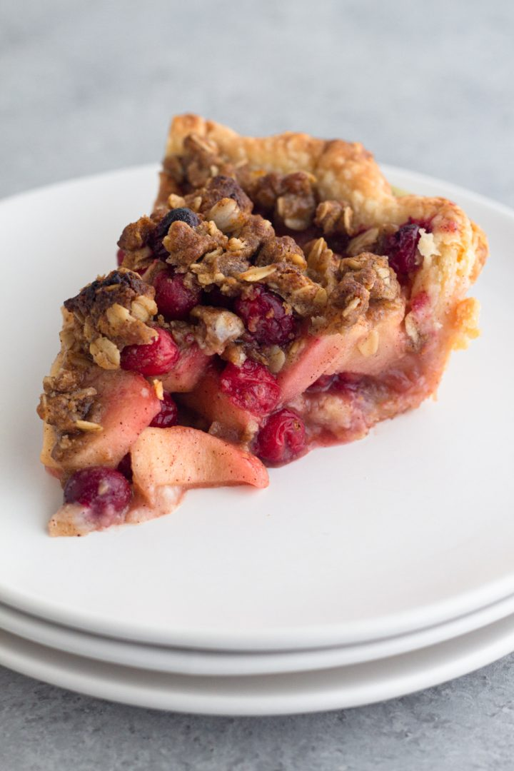 slice of apple cranberry crumb pie on a stack of white plates