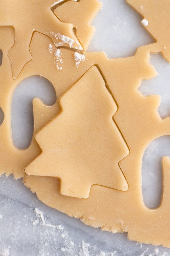 overhead view of sugar cookie dough with a Christmas tree cut out