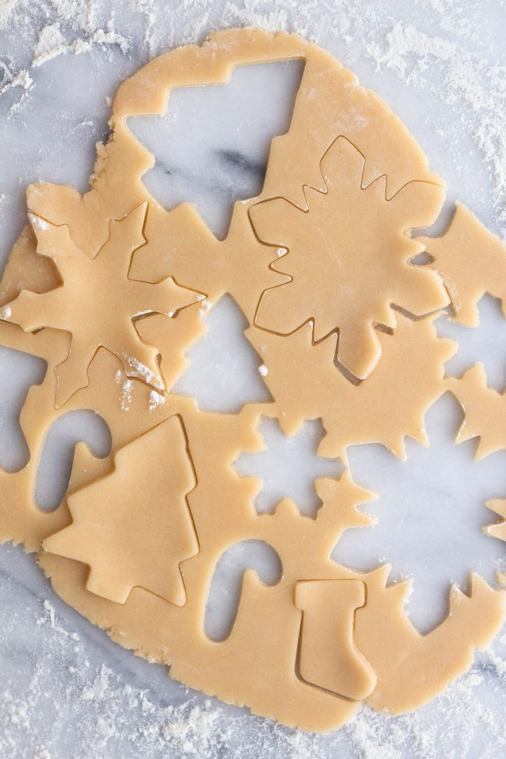 overhead view of sugar cookie dough with Christmas cookie cut outs