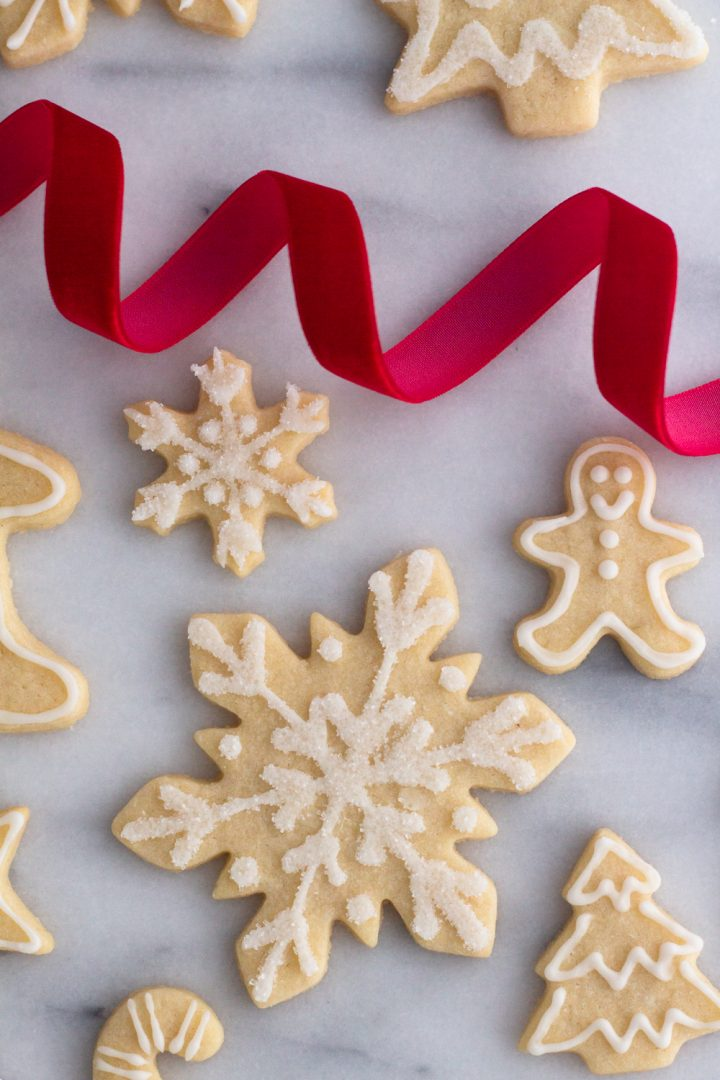 overhead view of cut out sugar cookies decorated for Christmas on a marble surface with a spiral of red velvet ribbon
