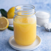 angled view of lemon curd in a mason jar next to fresh lemons and a jar of sugar on a speckled blue background