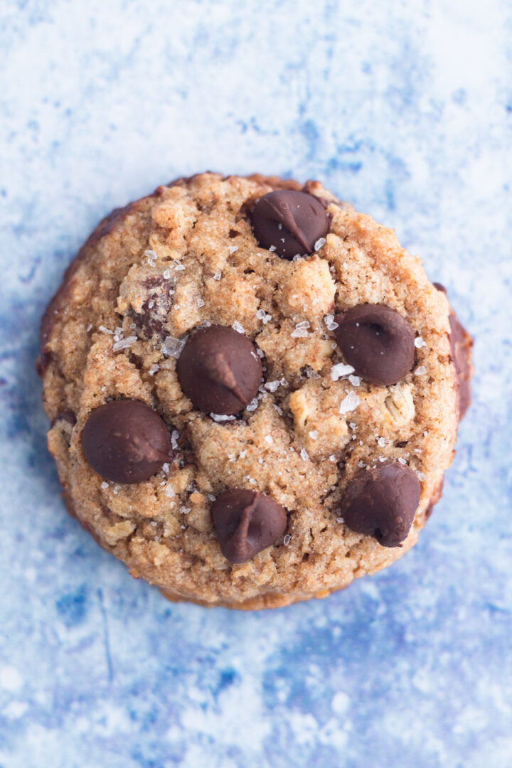 close up overhead view of a whole wheat chocolate chip cookie sprinkled with sea salt on a blue surface