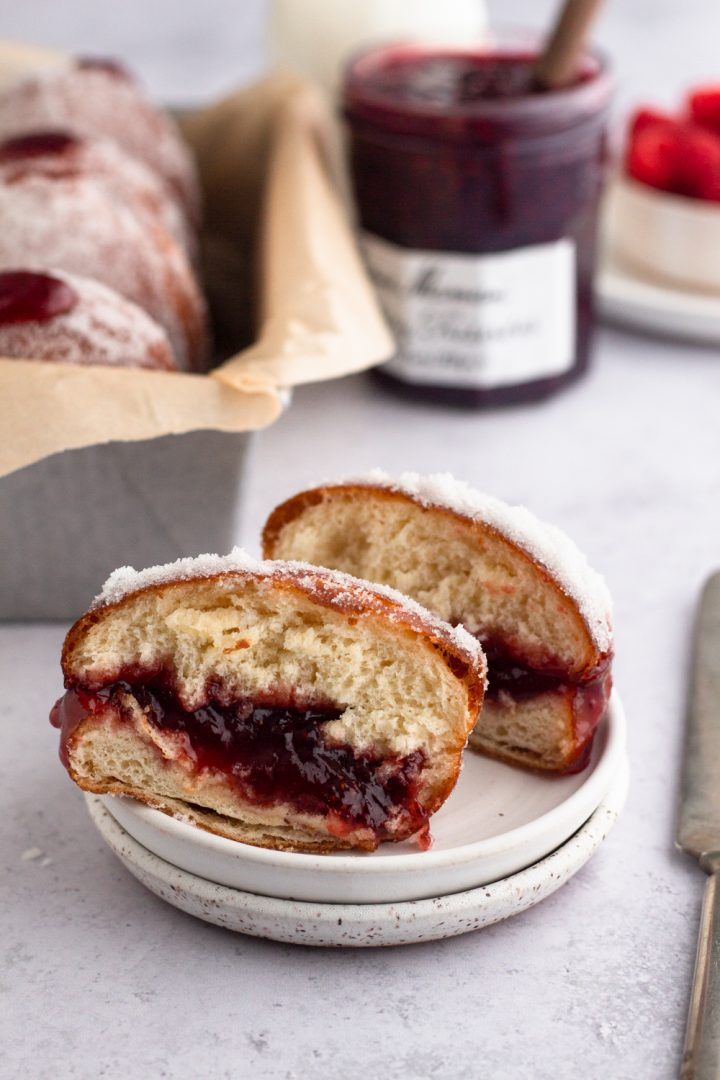 side view of a brioche jelly doughnut cut in half on a white plate with a loaf pan full of jelly doughnuts and a jar of raspberry jam in the background