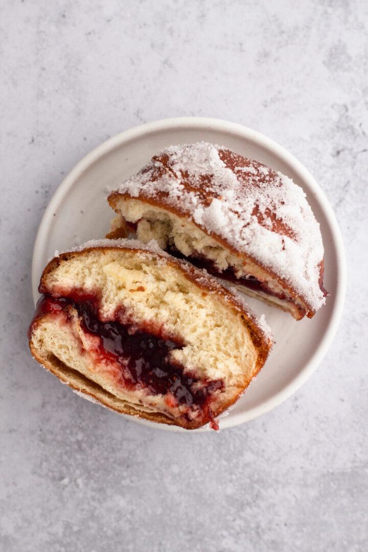 overhead view of a brioche jelly doughnut cut in half on a white plate