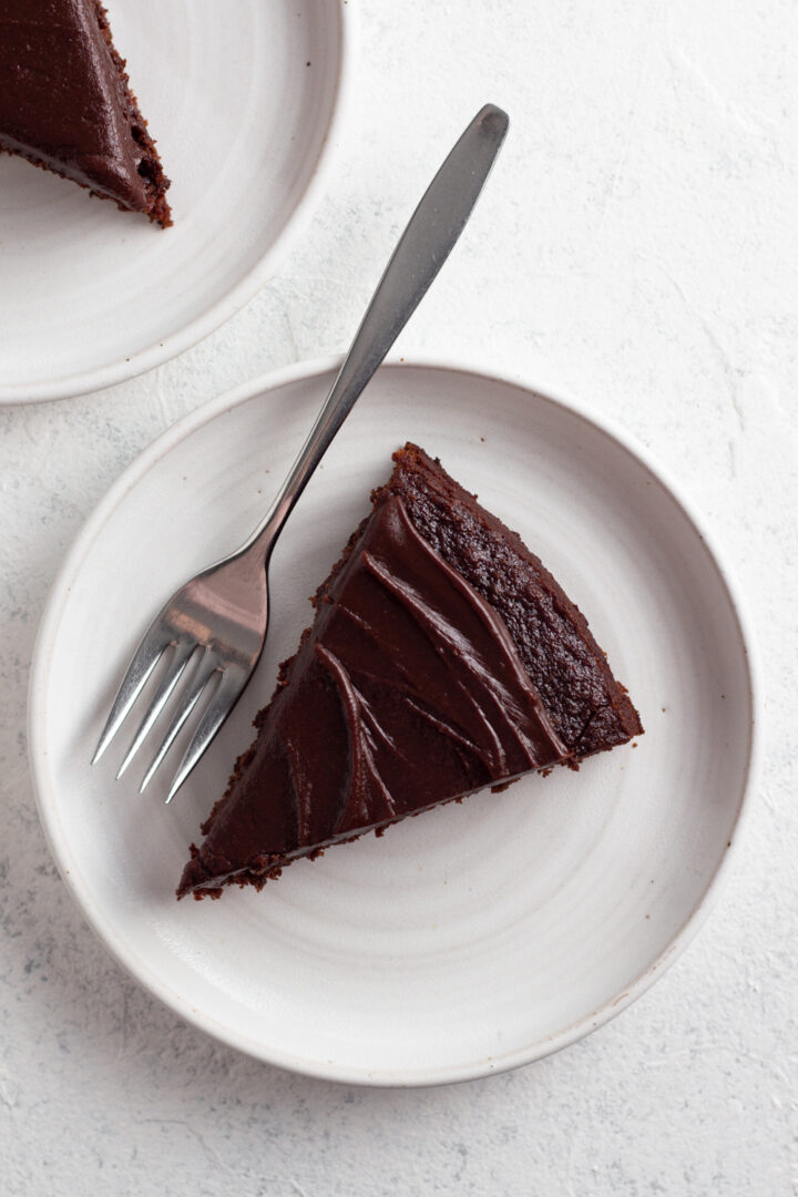 overhead view of a slice of fudgy chocolate cake on a white ceramic plate with a metal fork on a white background
