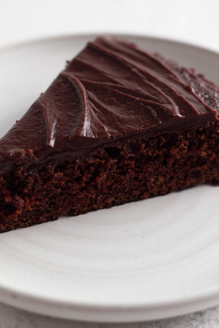 close-up side view of a slice of fudgy chocolate cake on a white ceramic plate