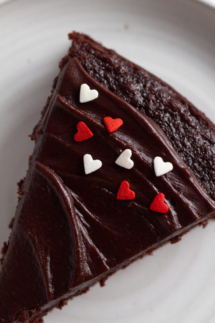 close-up overhead view of a slice of fudgy chocolate cake with red and white heart sprinkles on a white ceramic plate