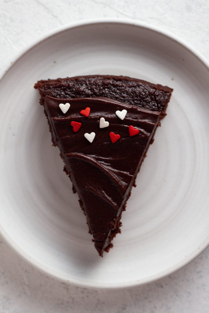 overhead view of a slice of fudgy chocolate cake with red and white heart sprinkles on a white ceramic plate