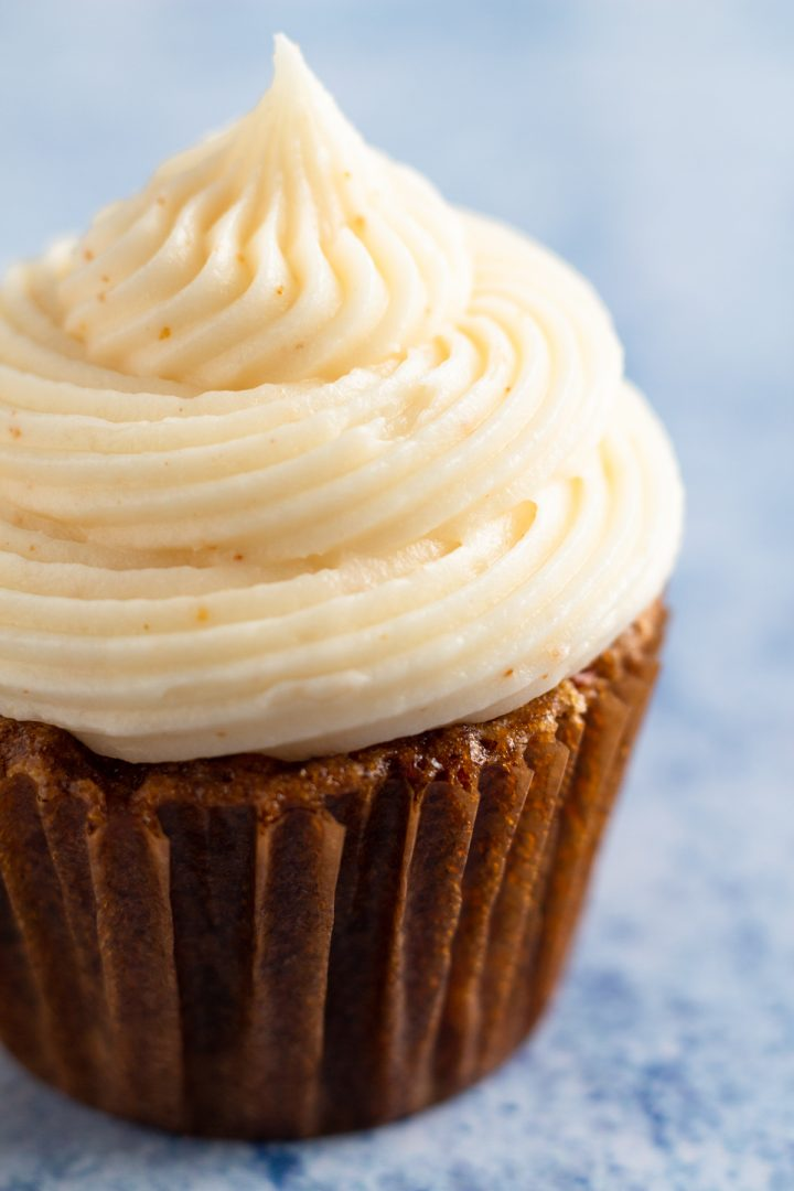 close up side view of a carrot cake cupcake with brown butter cream cheese frosting on a blue speckled background