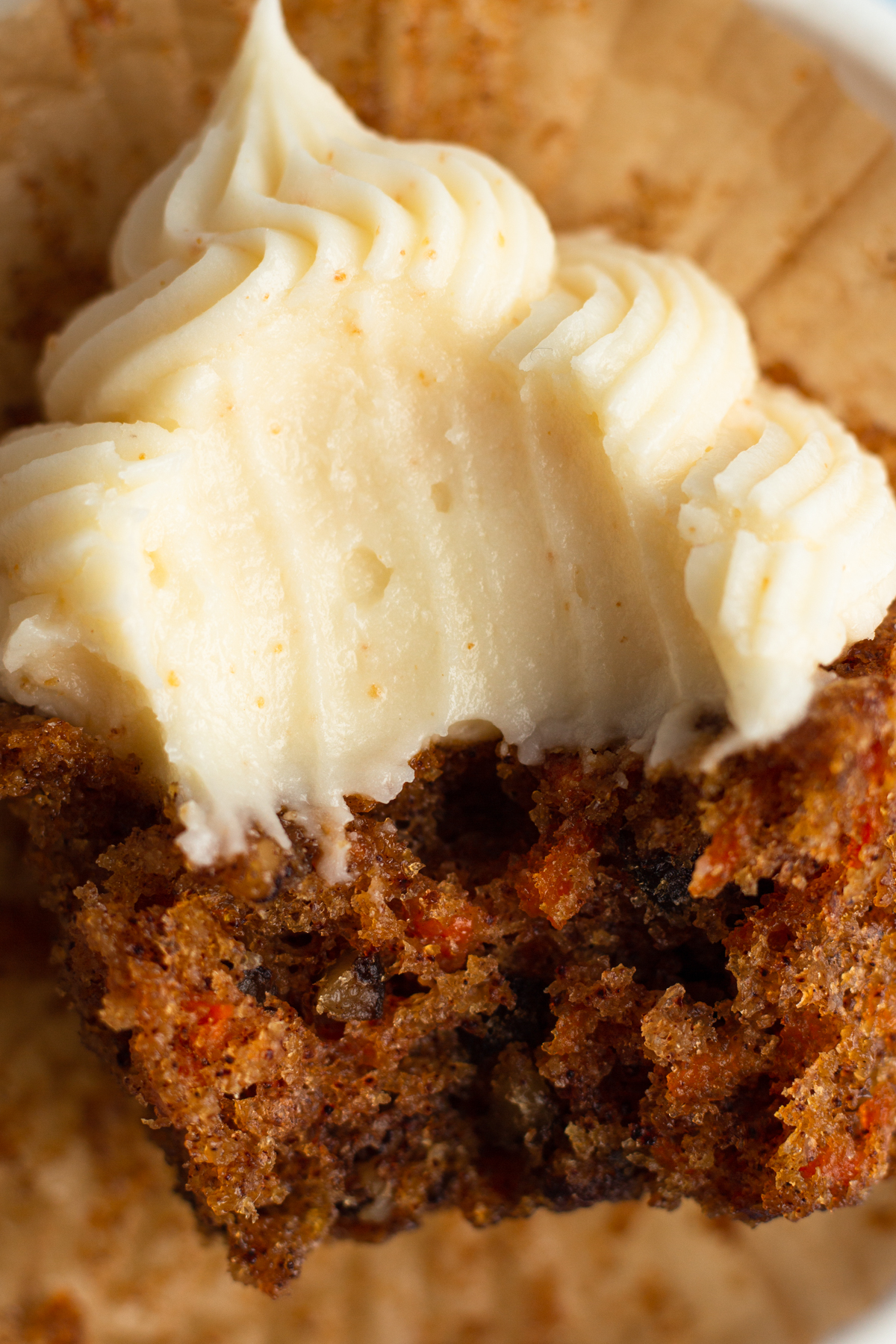 close up view of a carrot cake cupcake with a bite taken out