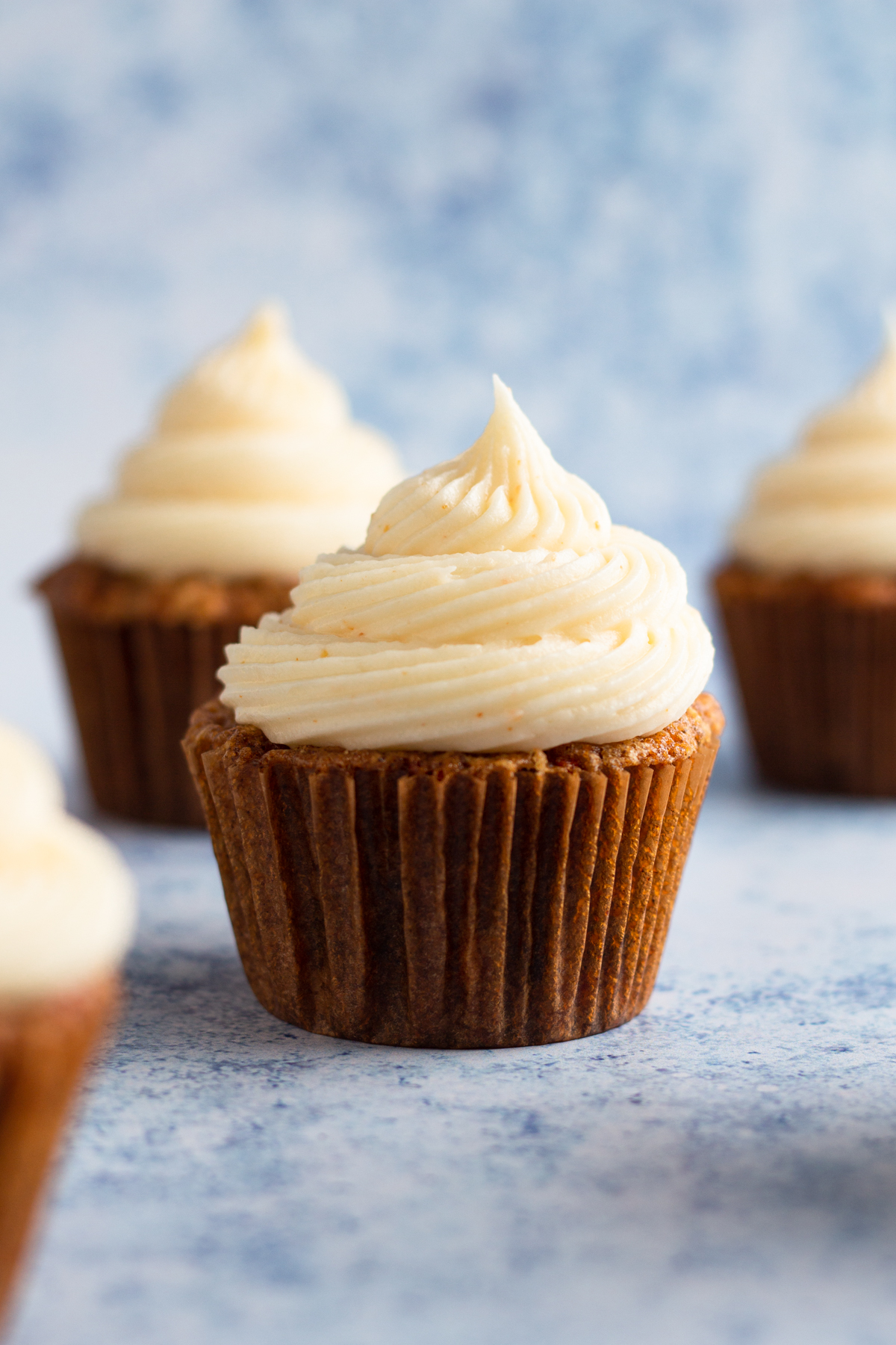 side view of carrot cake cupcakes on a blue speckled background