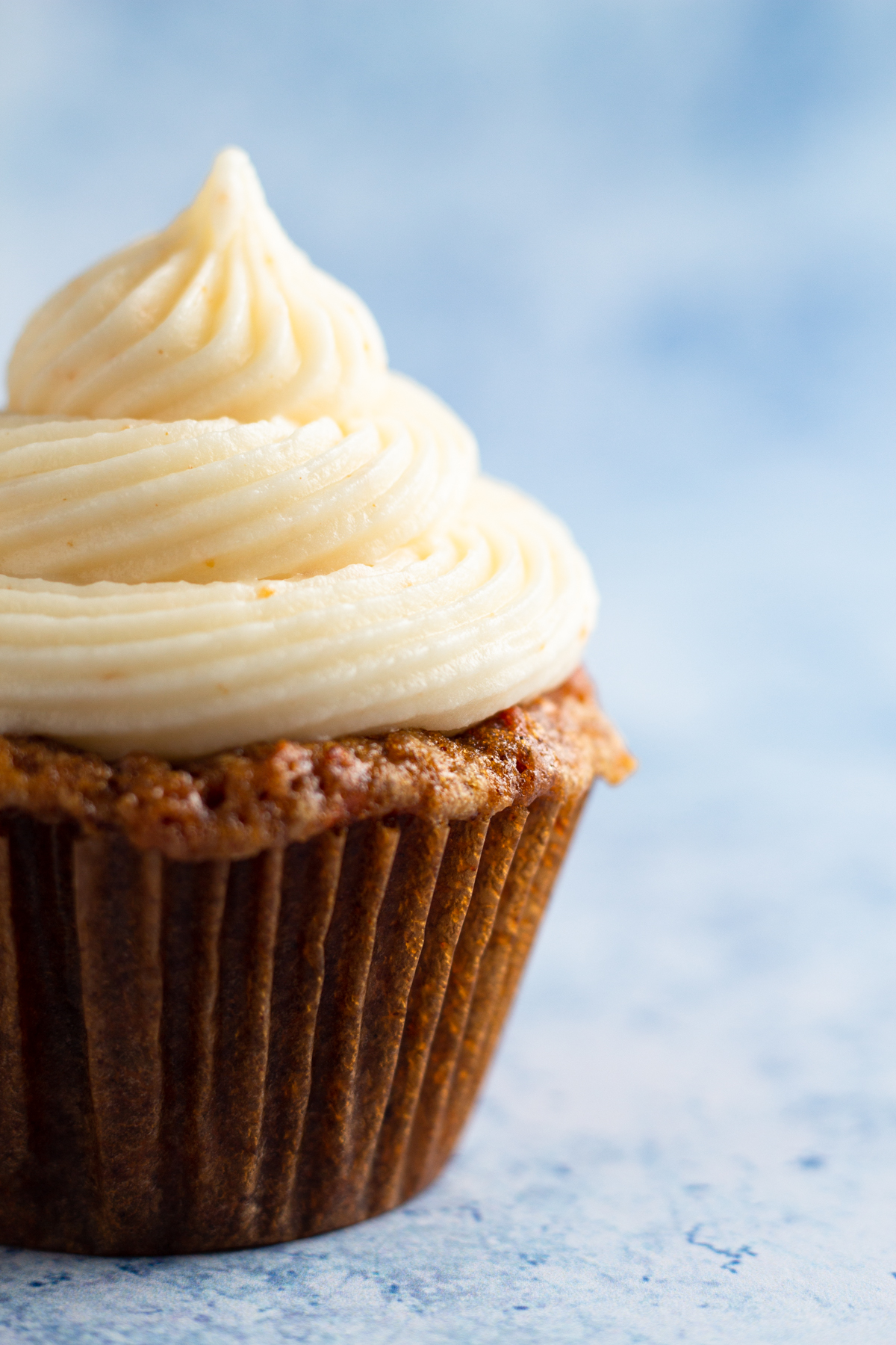 close up side view of a carrot cake cupcake topped with a swirl of cream cheese frosting