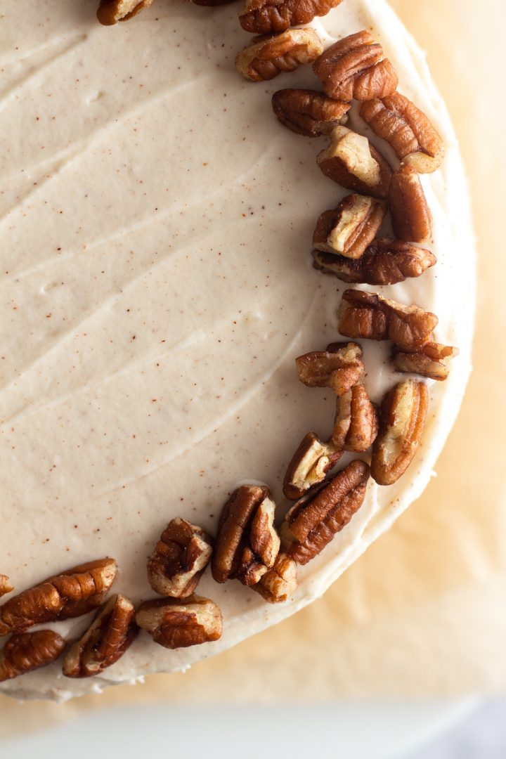 close up overhead view of a cake with cinnamon cream cheese frosting and a border of chopped pecans