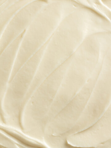close up view of cream cheese frosting spread on a cake
