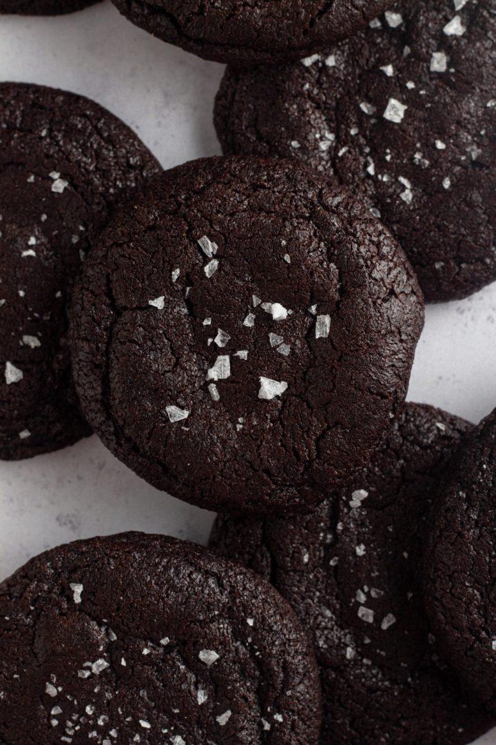 close up overhead view of chocolate cookies sprinkled with salt and scattered on a gray background