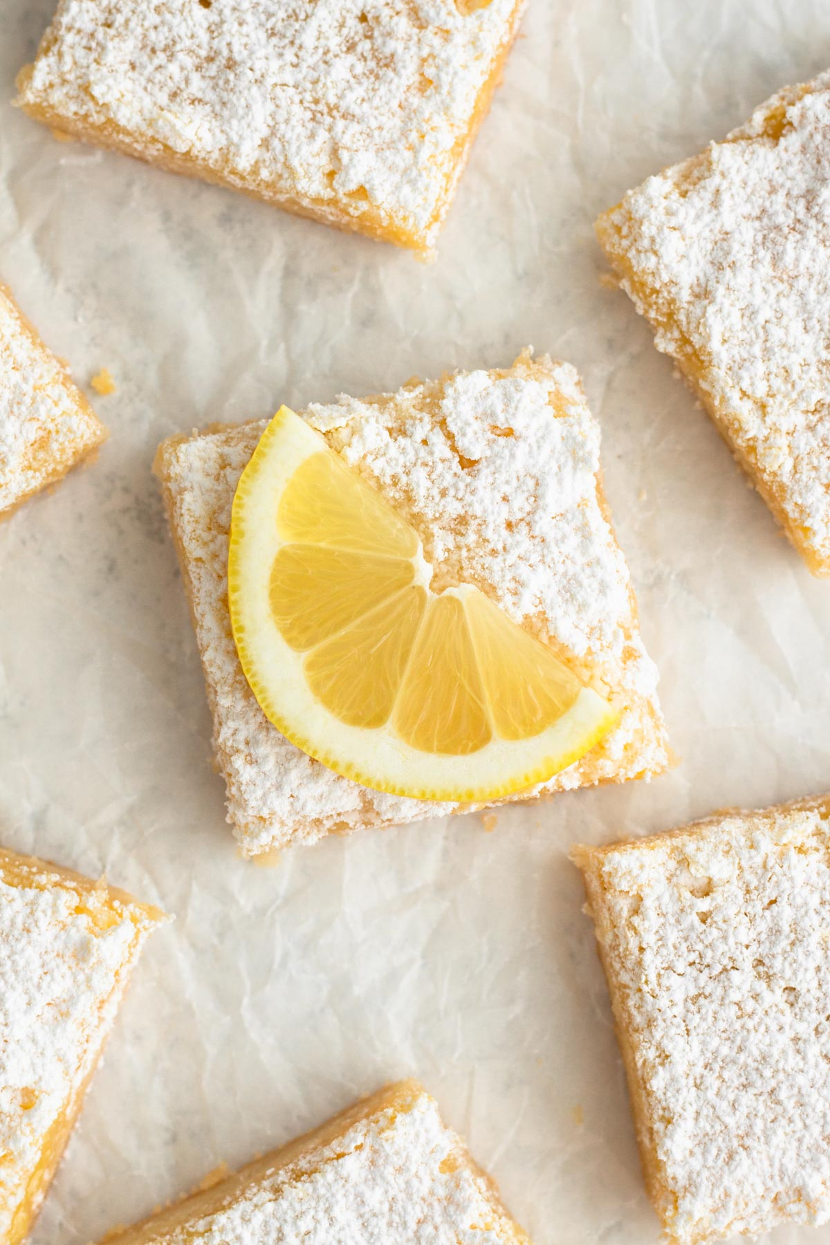 overhead view of a lemon bar and lemon slice on parchment paper