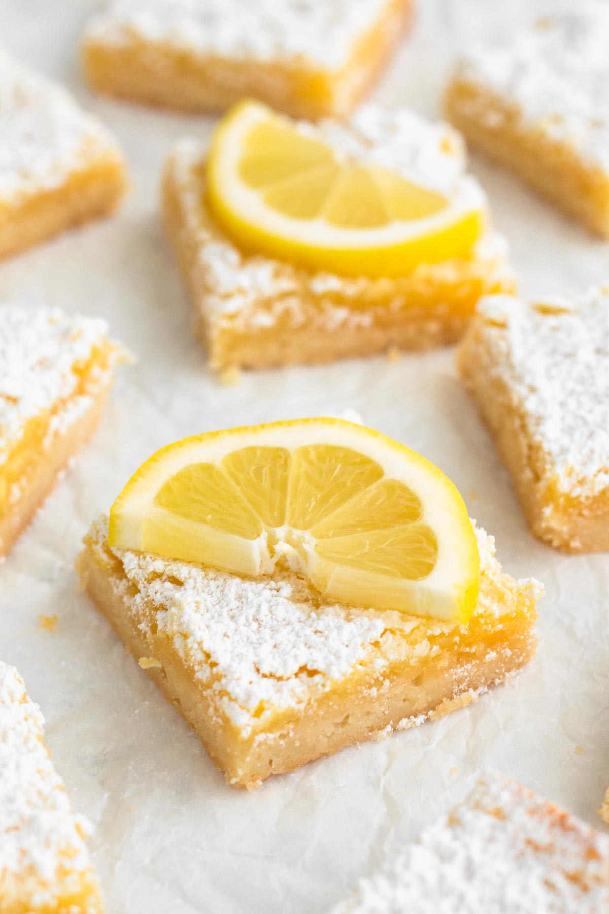 angled view of lemon bars and lemon slices scattered on parchment paper
