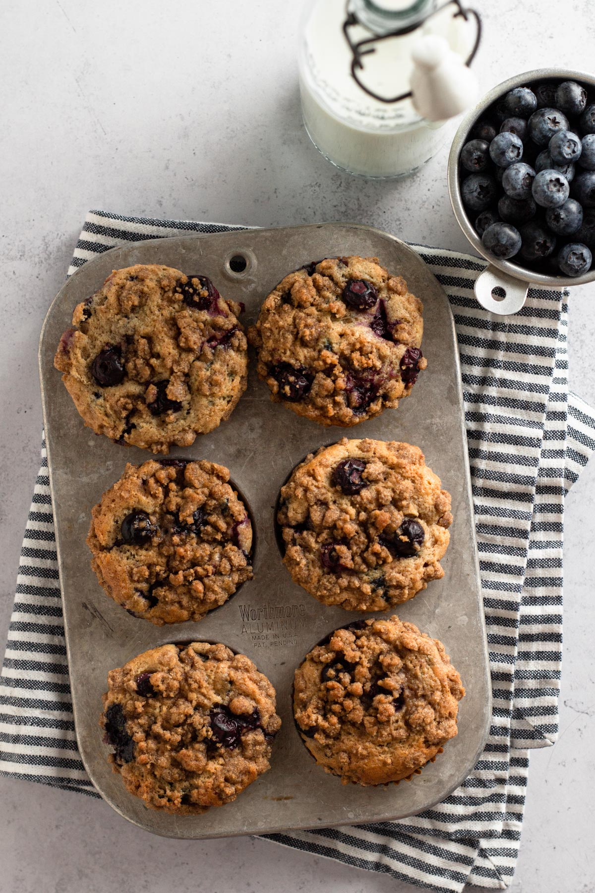 overhead view of muffins in an antique muffin pan with a striped napkin, jar of milk, and a cup of fresh blueberries