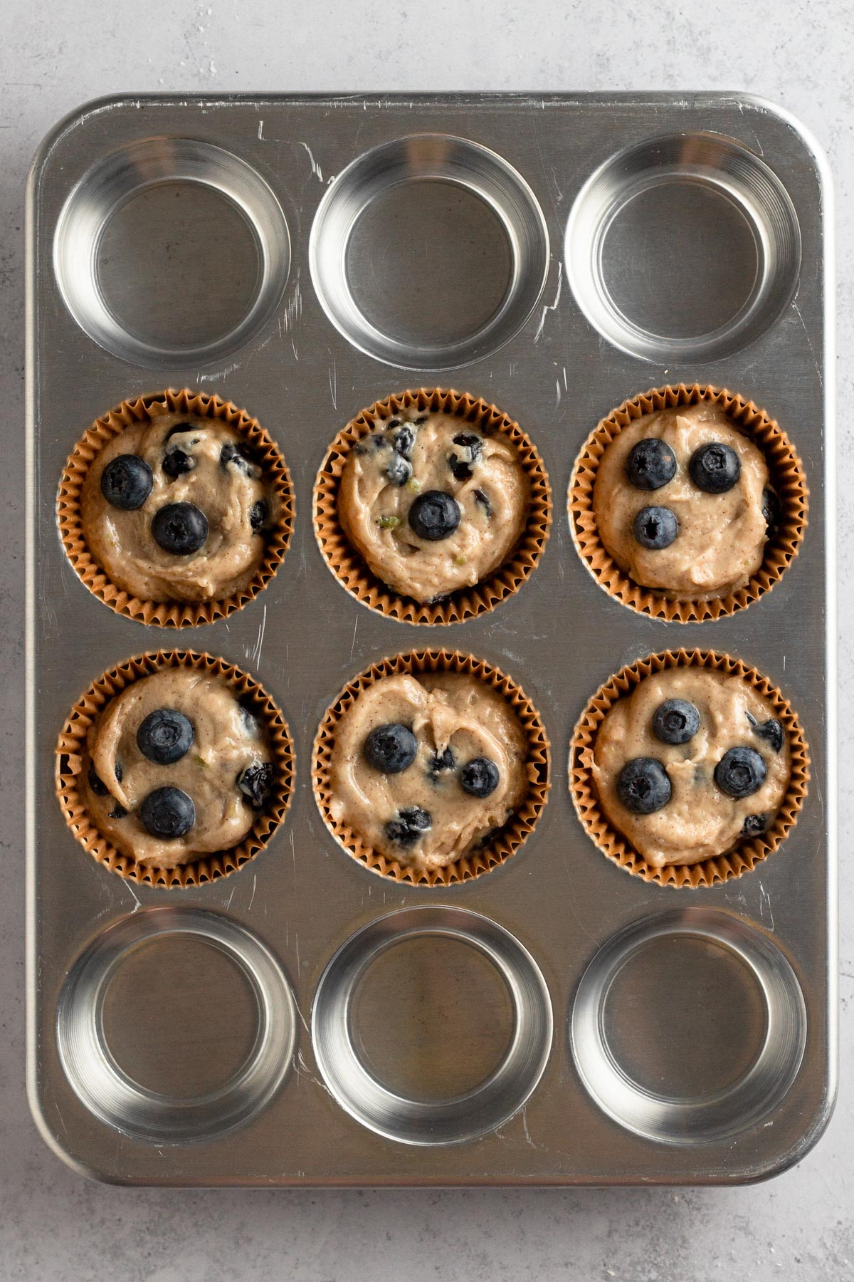 overhead view of muffin batter in brown paper liners in a metal muffin pan