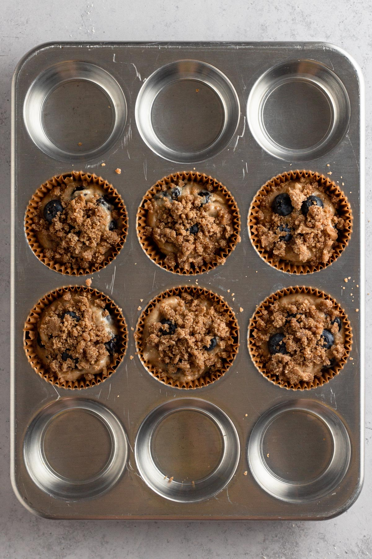 overhead view of streusel-topped muffin batter in brown paper liners in a metal muffin pan
