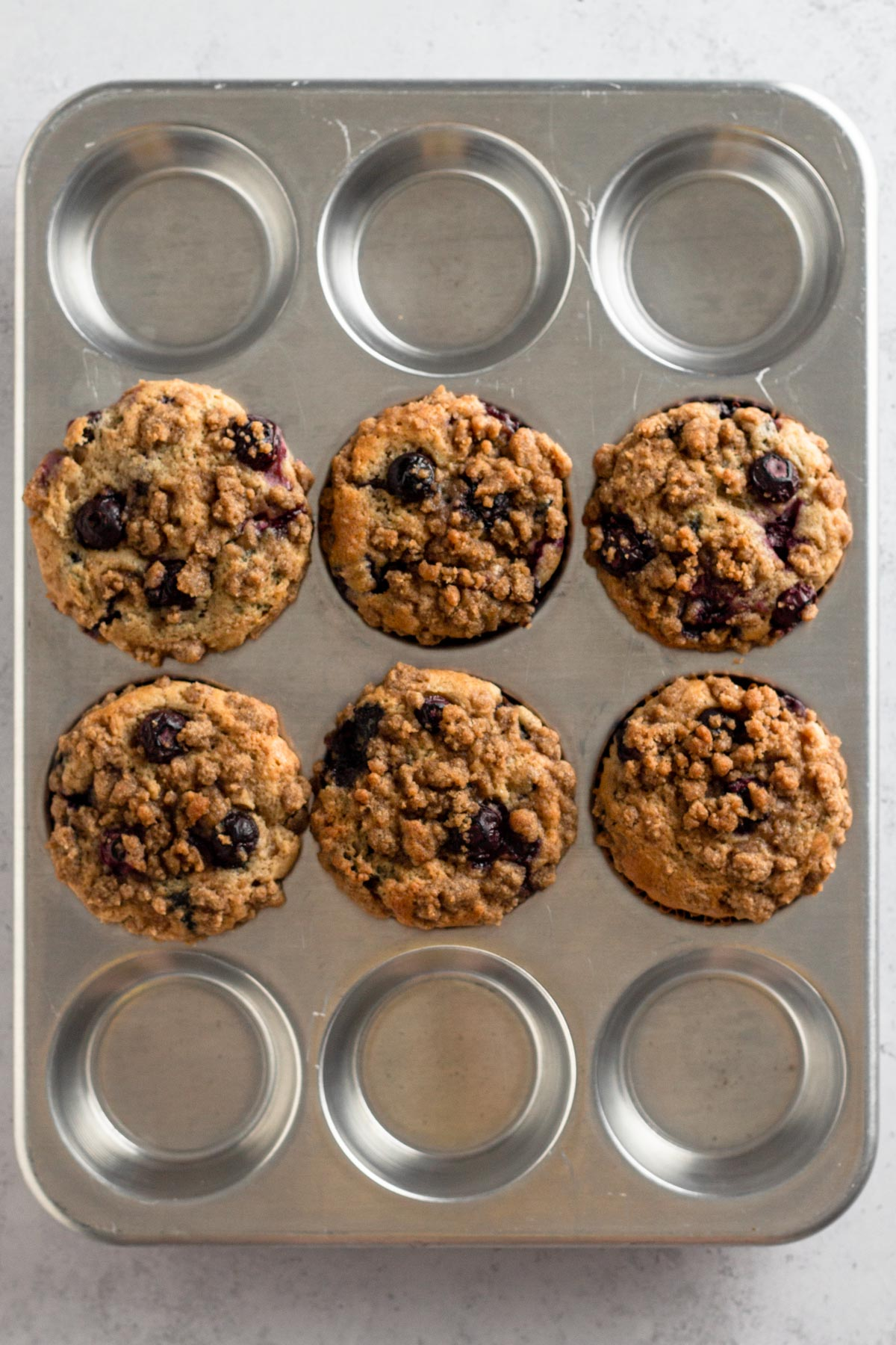 overhead view of baked blueberry muffins in a metal muffin pan